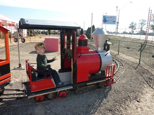 A three-year-old T taking a spin on a train at a local tree lot in Long Beach (CA). This happens to be the same train that is at our local pumpkin patch. The same family also runs a tree lot during the Christmas season and often brings the train back for the kids during the holidays (rides are free with a tree purchase, or $2-ish otherwise).