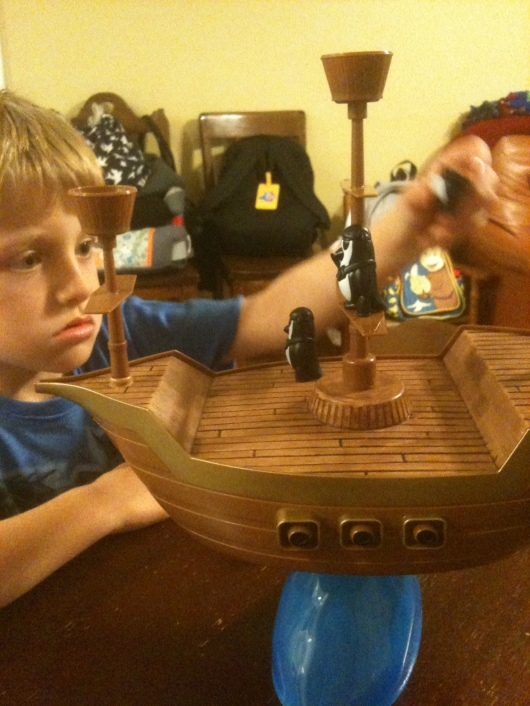 "T focuses hard on placing his penguin pirate atop the carefully balanced ship during the game ""Don't Rock the Boat."""