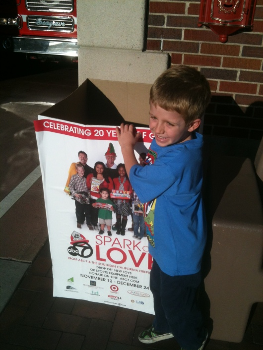 T drops some toys in the Spark of Love donation box outside of the fire station on 2nd Street in Long Beach (CA).