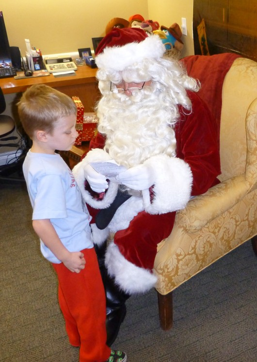 Santa looks over T's list. He kept it so that he has it for reference when he gets back to the North Pole to let his elves there know exactly what they need to make for T. That's what T said he kept it for anyway!