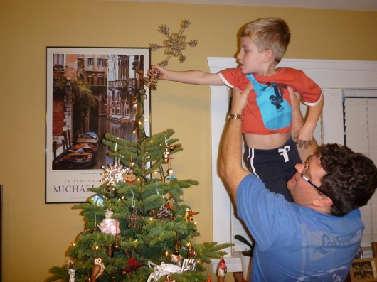 Another wonderful tradition: C holds T up to hang the star atop our Christmas tree. Love, albeit crooked.