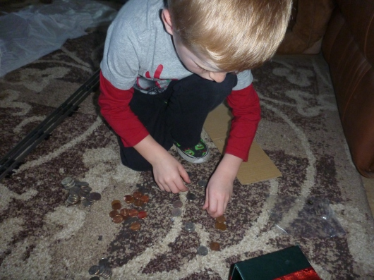 "T counts his coins from his first ""change grab,"" a new tradition his Memaw introduced this season and will incorporate for years to come."