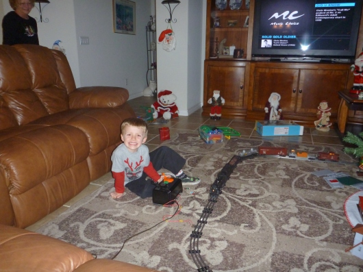 T enjoying his new train tradition (with box-o-change in the background), all thanks to his grandparents.