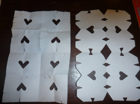 T's snowflake on the left, mine on the right. He wanted to cut fringe after folding his paper, and I helped him add the heart.