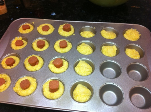 "Corn Dog Mini-Muffins are as easy as corn bread mix in a mini-muffin tin with a 1"" piece of hot dog stuck in center."