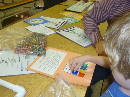 T makes a color blocking pattern in the math center at the school Math and Science Family Night Out.