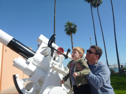 T and C look through a sight on a old military gun outside of the LA Maritime Museum.