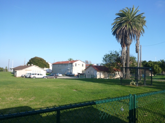This is a wide-shot of the cluster of buildings at the old Fort MacArthur base where you can find AGHR. Green fence in foreground; turn left immediately after this.