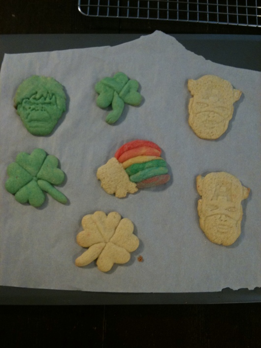"To make these shamrock sugar cookies, I took regular sugar cookie dough and dyed it green with regular food coloring, rolled it flat, and cut small hearts. Arrange three or four hearts point-side in to create either shamrocks or four-leaf clovers. Roll a small amount of green or regular cookie dough to finish with a stem. To make the rainbow, I reserved a small amount of sugar cookie dough to create the colored bands, dyeing each band with regular food coloring. I finished with a ""cloud"" of plain dough at one end. You could also make a pot-o-gold instead of the cloud."