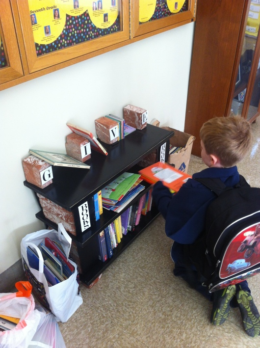 T placing his donations on the shelves for his school's used book drive. This was held as part of the activities for Read Across America 2013.