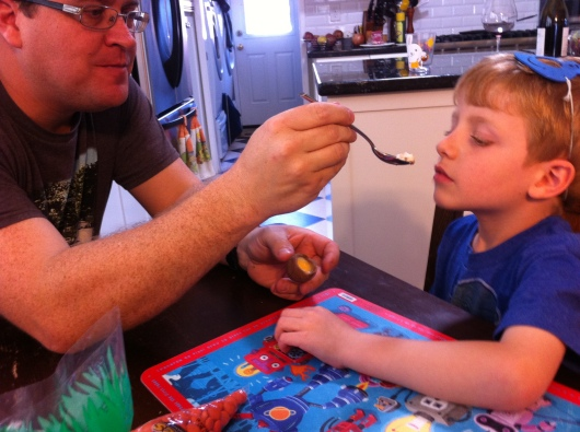 Dad readies a spoonful of the innards of a Cadbury Creme Egg for T to try for the first time.