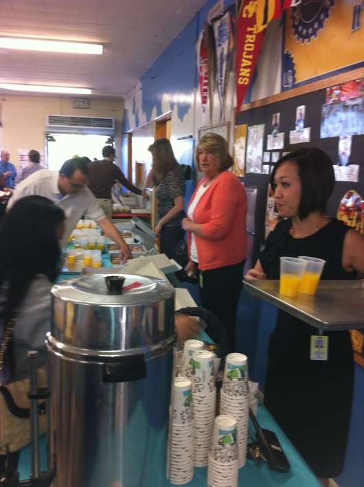 T's teacher (mid-photo) and Principal (L) help distribute the goods on Mom Muffin (Donut) Day last Friday at school.