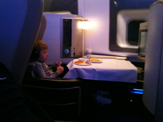 T enjoying his dinner aboard BA First, a ham and cheese tea sandwich with carrot sticks. I think he also got some fruit and ice cream for dessert after this, so his meal was three-course as well.