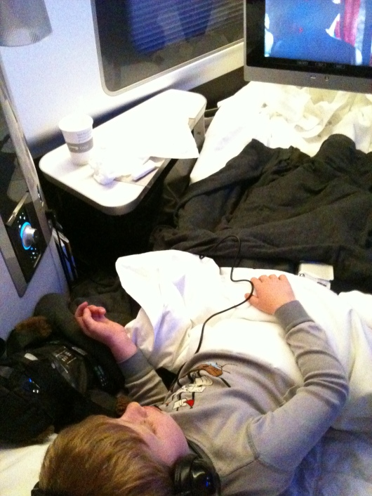 "T in his ""bed"" in BA's First cabin during our flight from LAX to LHR."