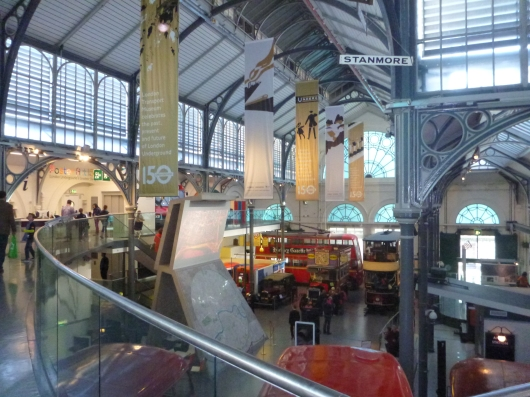 A wide view inside the London Transport Museum. High ceilings needed as there are many large vehicles on display.