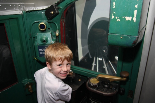 This was one of the Underground driving simulators. T works the driving gears and brakes to get his train to stop at the Underground platform. He did great!