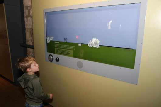 T playing a trajectory-simulation game at the Tower of London inside of White Tower.