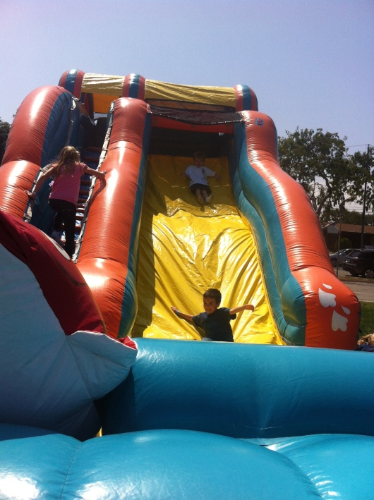 T and his buddy sliding at their school carnival.