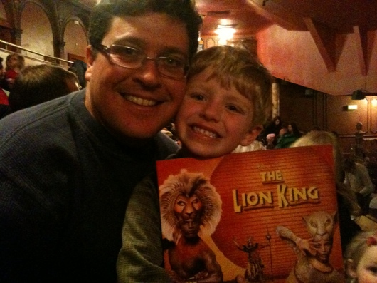 C and T with the program from The Lion King inside the Lyceum Theatre, London.