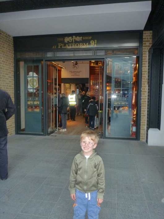 T outside the Harry Potter Shop near Platform 9-3/4 at King's Cross Railway Station, London.