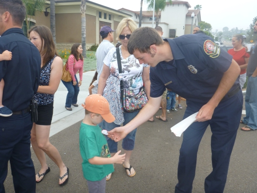 T gets stuck with stickers by a firefighter during the La Mesa Firefighters Local 4759 pancake breakfast last Sunday.