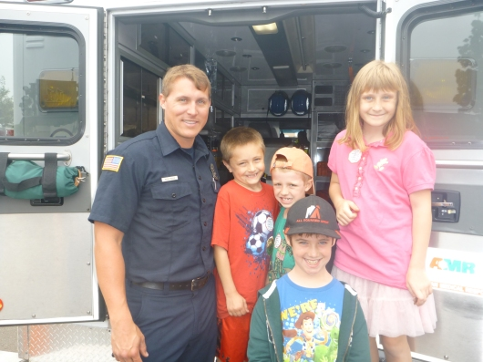The kids pose with a paramedic who had his truck open and on display during the pancake breakfast at La Mesa Fire Station 11 last Sunday.