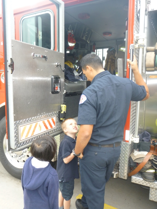 T asking the fire fighter a question before getting into the cab of the fire engine. No idea what he was asking. He asked a lot of questions that morning!