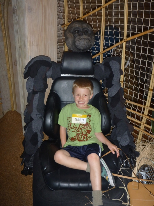 "T sits on the gorilla's ""lap"" (an old car seat) at Noah's Ark."