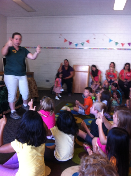 "Wildlife Learning Center educator Alicia shows the audience that a ""thumbs up"" is the appropriate response to when we see something we like. Loud noises tend to spook the animals, so it was an applause-free afternoon, but one with many more than just two thumbs-up!"