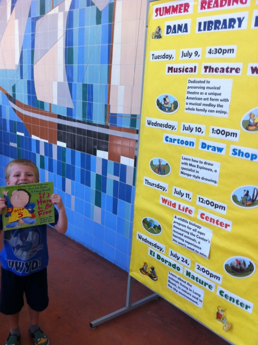 T showing off his free book for concluding the summer reading program: It's Hard to Be Five by Jamie Lee Curtis. Great choice, T!