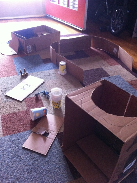 Over the weekend, T made a Bat-cave, a baseball diamond (complete with dugouts, backstops, and bases), and something else I can't remember right now. The cups are for when he needs to fire his foam dart gun at-will at something other than the furniture, windows, and doors. Yep, this is T's world!