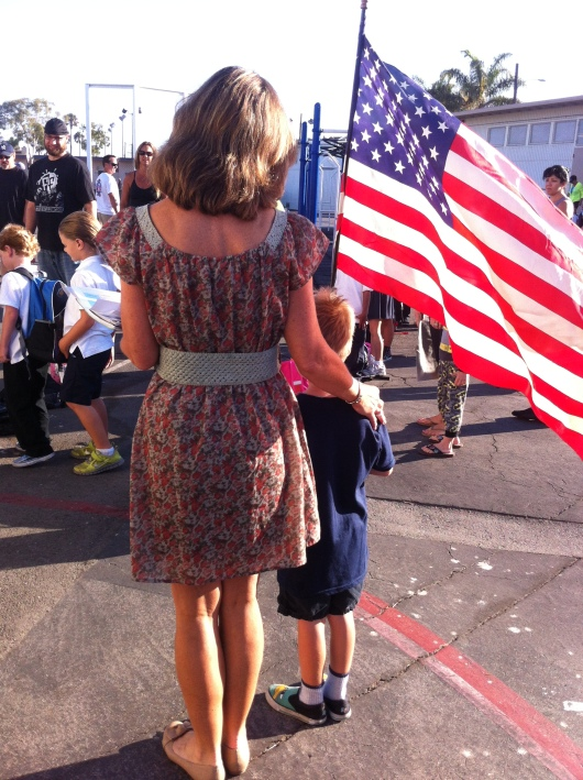 Mrs. K guides T through the crowd toward the assembly area on the playground.