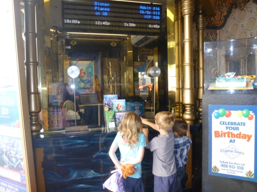 The kids peeking into the box office at the El Capitan Theatre.
