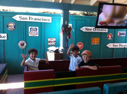 T with his two new friends on the train at Adventure City.