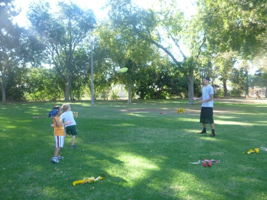 Coach Chris warming up two kids at once at the first flag football practice of the season!