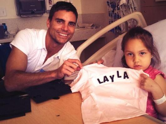 "Colin Egglesfield reading to a pediatric patient at Children's Hospital Los Angeles as part of their ""Literally Healing"" program. Egglesfield plans to participate in a similar outreach here in Long Beach at Miller Children's Hospital to help the kids kick off the holiday season."