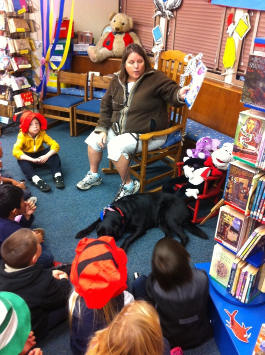 A BARK volunteer human and her volunteer pup read at our school as part of our Read Across America events.