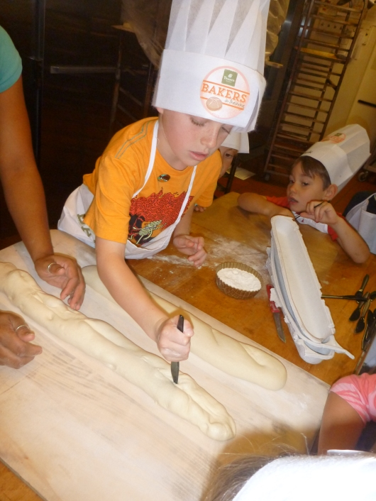 T popping a bubble in his dough. If left the loaf would bake unevenly and with a large hole inside, so the kids were encouraged to pop all the bubbles before their loaf went into the oven.