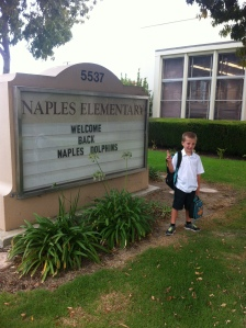 Traditional first day of school photo in front of school sign (combo face).